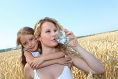 picture of drinking water  - Mother drinking water in wheat field with child - JPG