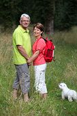 Senior couple rambling in countryside hand in hand
