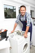stock photo of washing machine  - Plumber fixing broken washing machine - JPG