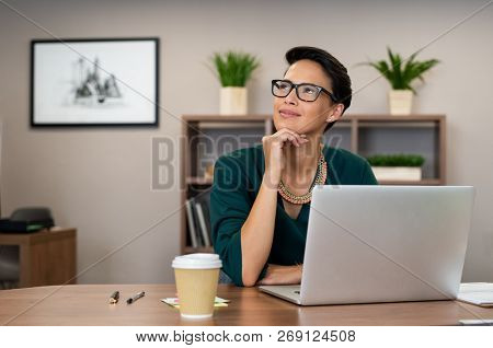 poster of Thoughtful fashion business woman working on a laptop and looking up. Beautiful glamour girl daydrea