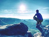 Fearless Man In Sportswear Is Sitting On Cliff Edge And Looking To Far Horizon. poster