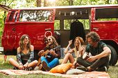 Group of friends hippies men and women laughing and playing guitar near vintage minivan into the nat poster