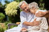 Senior man in medical patient cloth hugging wife outdoor bench. Old woman is consoled by her husband poster