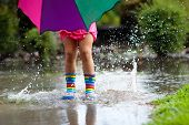 Kid With Umbrella Playing In Summer Rain. poster