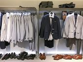 Men clothes row of clothes, suit, jacket, shoes, on the racks in clothing store  poster