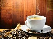 picture of wooden table  - hot coffee with smoke on the grange background - JPG