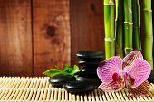 spa frame from bamboo grove, pink orchid and black zen stones on the old wooden backgroun