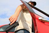 Man holding gun entering to red car