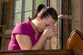 stock photo of pry  - Young woman prying in the church - JPG