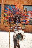 TULUM, MEXICO - JULY 15: Unidentified man in Mayan traditional ornamental feather headdress dances t