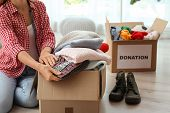 Woman Packing Clothes Into Donation Box At Home poster