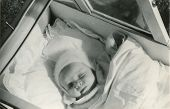 Vintage unretouched photo of baby girl in old-fashioned pram (1954)