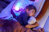 Little Preschool Kid Boy Sleeping In Bed With Colorful Lamp. School Child Dreaming And Holding Plush poster