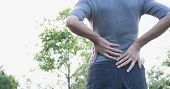Closeup Hands Of Woman Touching Her Back Pain In Healthy Concept On Nature Background. poster