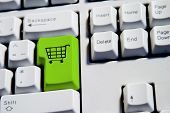stock photo of internet shop  - computer keyboard from a desktop computer with the enter key highlighted in green with a large shopping cart on it - JPG