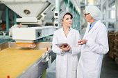 Portrait  Of  Two  Female Workers Doing  Production Quality Inspection In Food Factory Standing By C poster
