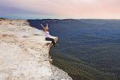 Woman Sits On Edge Of Cliff With Arms Up Full Of Happiness And Vitality poster