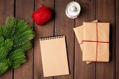 Holiday Flatlay, Gifts Wrapped With Craft Paper, Notebook With Blank Paper And Fir On A Rustic Dark  poster
