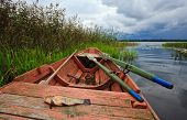 Summer's Lake Scenery With Wooden Boat And Fish Before The Storm