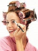A young young woman applying makeup mirror.