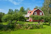 stock photo of manicured lawn  - Picturesque traditional red painted wooden house in Sweden in a lush green landscaped garden with manicured trees - JPG