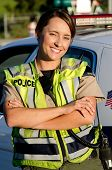 foto of lightbar  - a female police officer smiling as she crosses her arms in front of her partrol car - JPG
