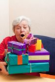 Senior Sitting On The Couch With Gifts