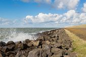 Golven in de buurt van een Nederlandse golfbreker met Windturbines