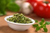 stock photo of oregano  - Dried oregano leaves in small bowl with fresh oregano on the side tomato garlic and basil in the back  - JPG