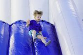 picture of inflatable slide  - Boy slides down an inflatable slide - JPG