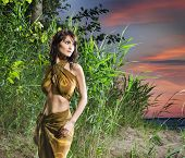 stock photo of cannibal  - Attractive savage woman is posing in the jungle over the sunset background - JPG
