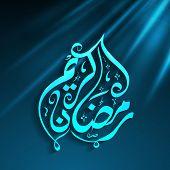 Arabic Islamic calligraphy of text Ramadan Kareem on shiny blue background.