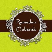 Ramadan Mubarak text on floral decorated frame on green background.