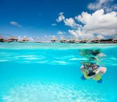 Woman snorkeling in clear tropical waters in front of overwater villas