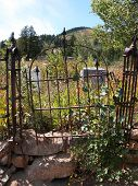 pic of burial  - A gate hangs crooked at this burial plot in an Idaho ghost town - JPG
