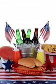 Closeup of a picnic table decorated for the Fourth of July. Vertical format with a white background. Items include a bucket full of beer bottles, hot dog buns, watermelon, flags and chips.