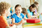 stock photo of classmates  - Portrait of happy pupil looking at her classmate at lesson - JPG