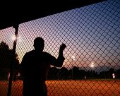 a silhouette of a baseball/softball player in the dugout