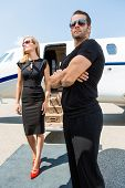 foto of bodyguard  - Elegant woman with bodyguard standing against private jet - JPG