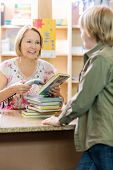 picture of librarian  - Young boy standing at checkout counter while librarian scanning books in library - JPG