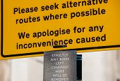 pic of saying sorry  - Please seek alternative routes where possible warning yellow sign on the city street - JPG