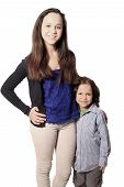 pic of babysitter  - Older sister or babysitter standing beside little brother on a white background - JPG