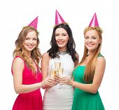celebration, drinks, friends, bachelorette party, birthday concept - three smiling women wearing pink hats with champagne glasses