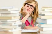 Bored student girl between stack of books looking up glasses