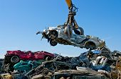 stock photo of landfills  - Crane picking up a car in a junkyard - JPG