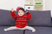 stock photo of leg-split  - Baby girl doing legs splits on sofa - JPG