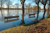 stock photo of flood  - Partially submerged benches on a flooded riverbank in Windsor - JPG