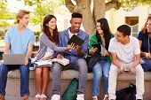 stock photo of playground school  - High School Students Collaborating On Project On Campus - JPG