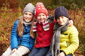 Three Children On Walk Through Winter Woodland