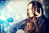 Beautiful expressive girl listening to music in headphones. Disco, party.